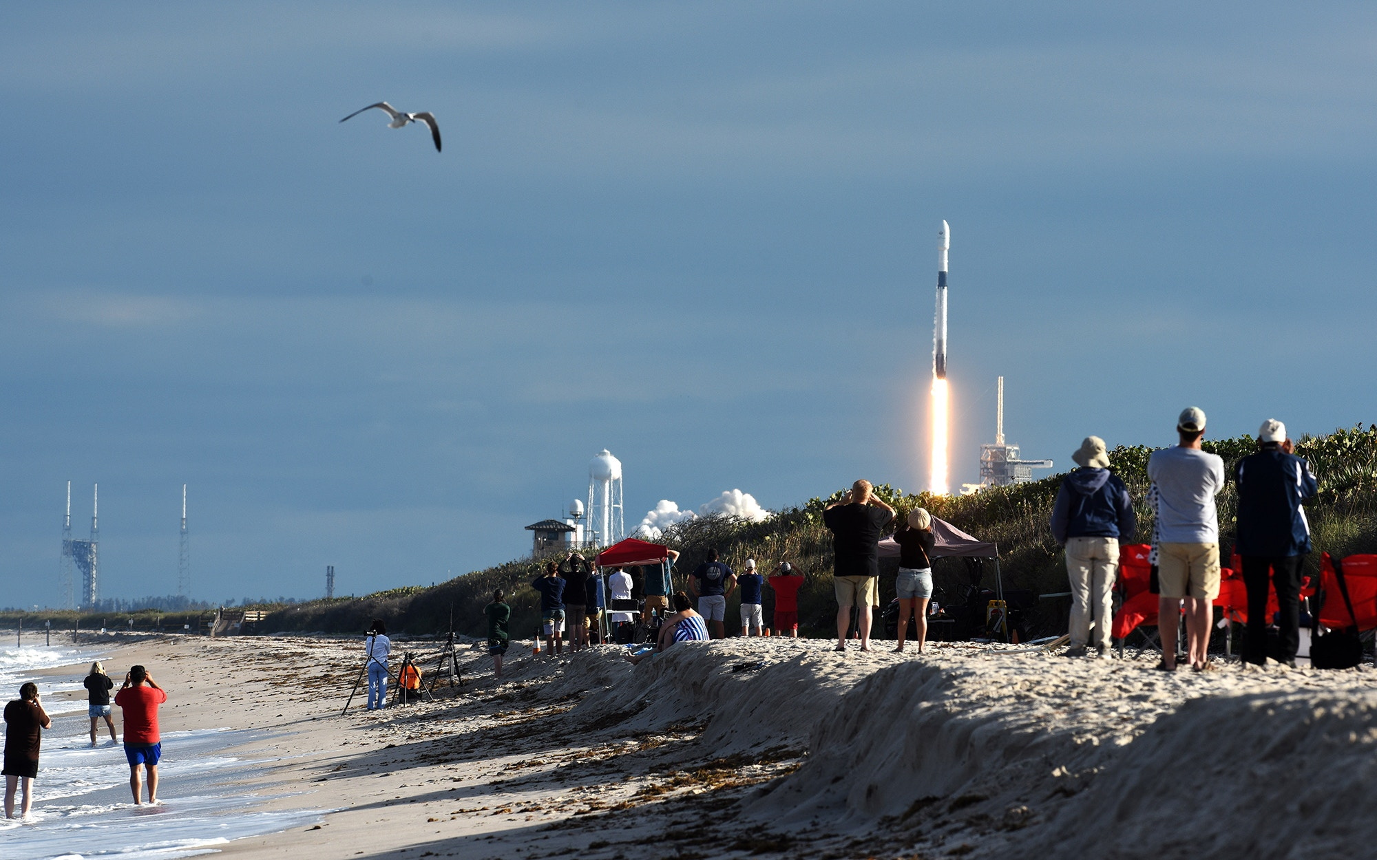 People watch as a SpaceX rocket takes off from Canaveral National Seashore