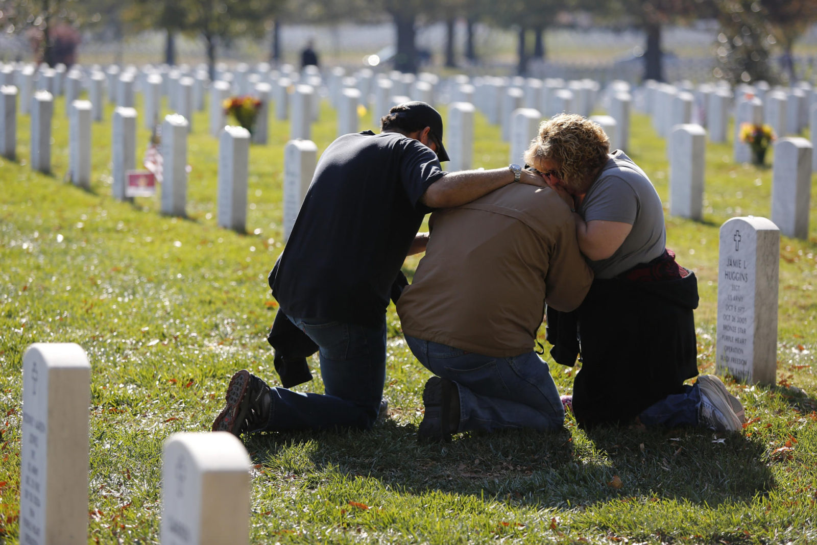 People grieve at a gravesite in Section 60, an area where members of the U.S. military who were killed in action in Iraq and Afghanistan are buried, during Veterans Day observances at Arlington National Cemetery in Arlington, Virginia, November 11, 2012. REUTERS/Jonathan Ernst (UNITED STATES - Tags: POLITICS MILITARY)
