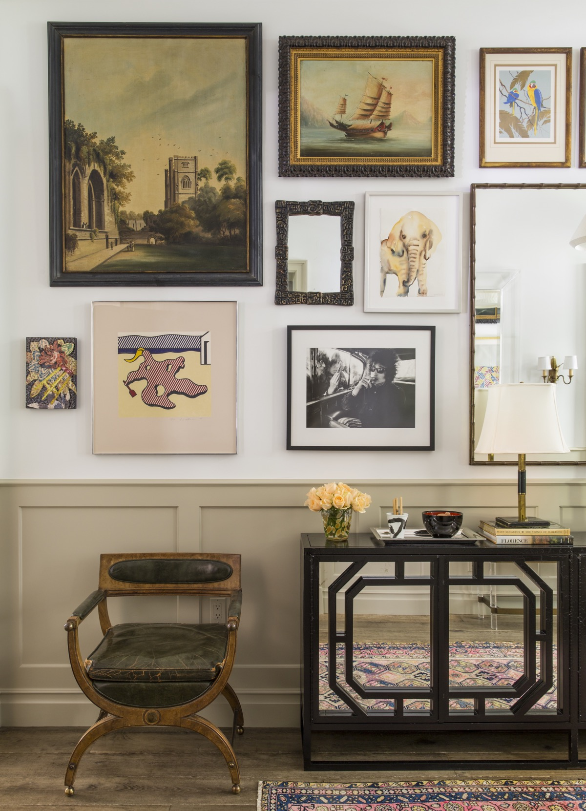 Entry hall with wood and leather chair, dark wood wall table with mirrored front, lamps, flowers and tray in front of light wall with various mirrors, paintings and photos.