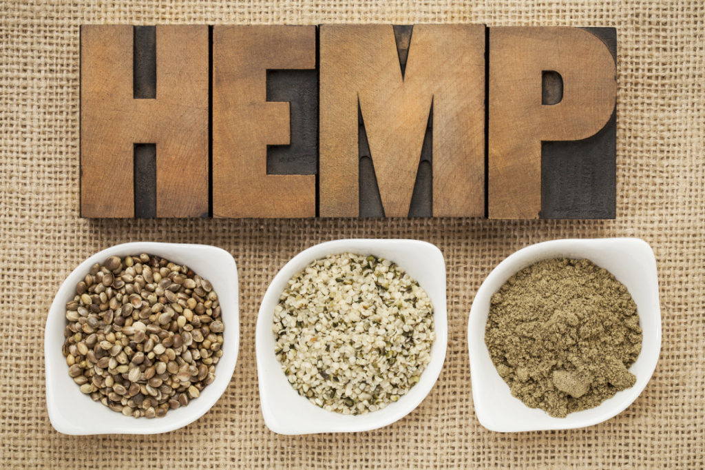 hemp products: seeds, hearts (shelled seeds) and protein powder in small ceramic bowls on burlap canvas with word hemp spelled in letterpress wood type