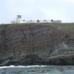 St. Ann's lighthouse and cliffs of layered Old Red Sandstone