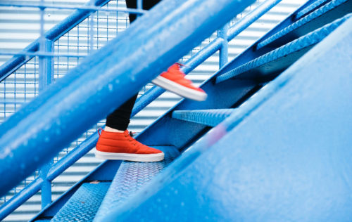 Image of person wearing orange trainers running up steps