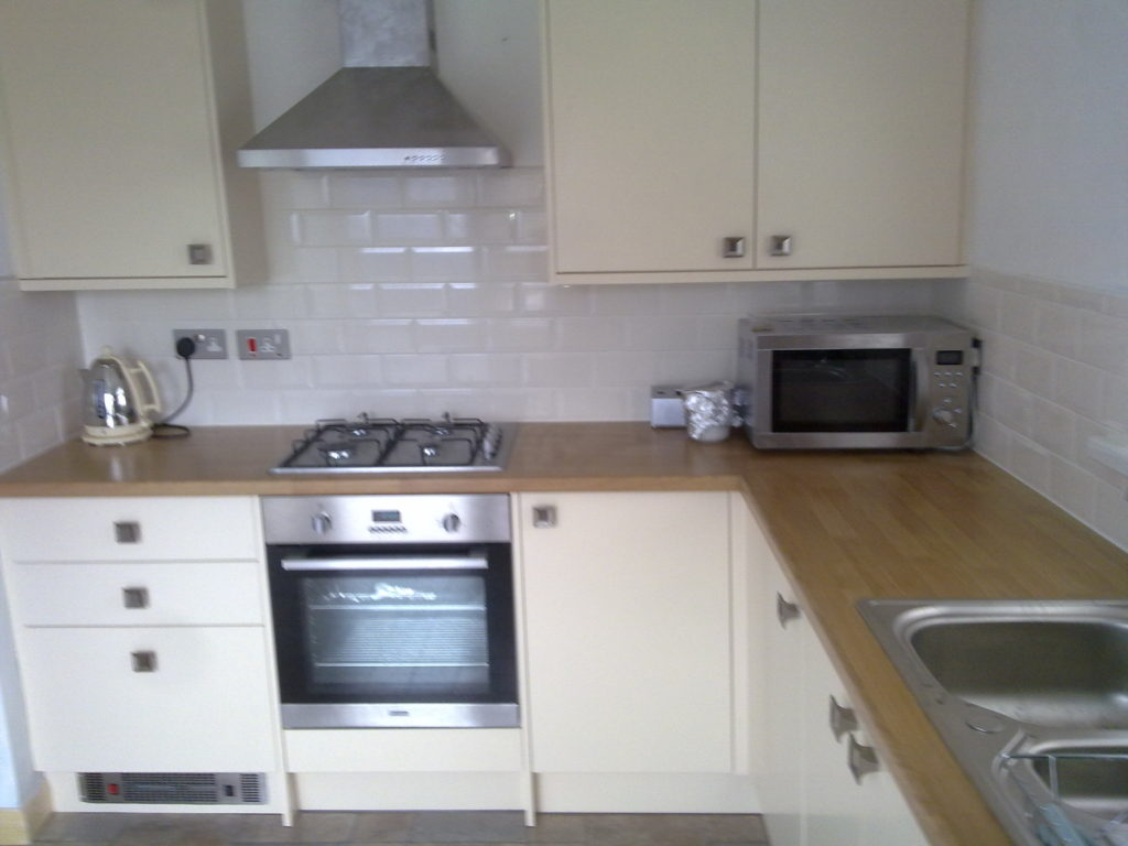 Cream kitchen with white tiles, stainless extractor and plynth heater