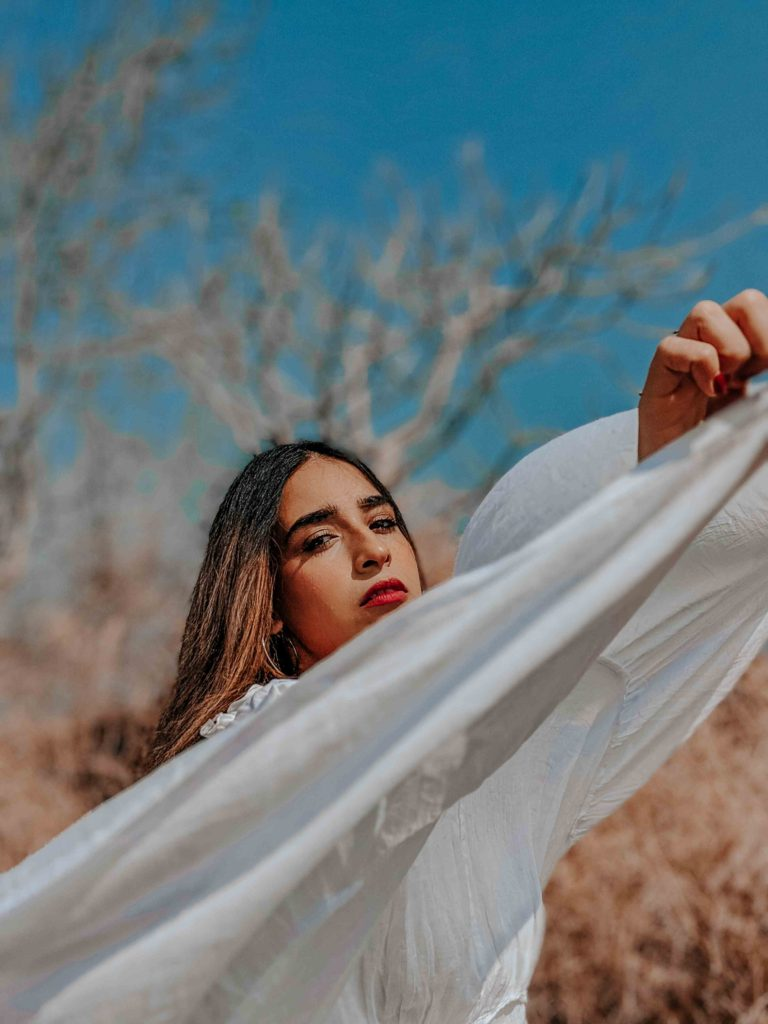 Outdoor editorial fashion shoot with girl in white flowy dress