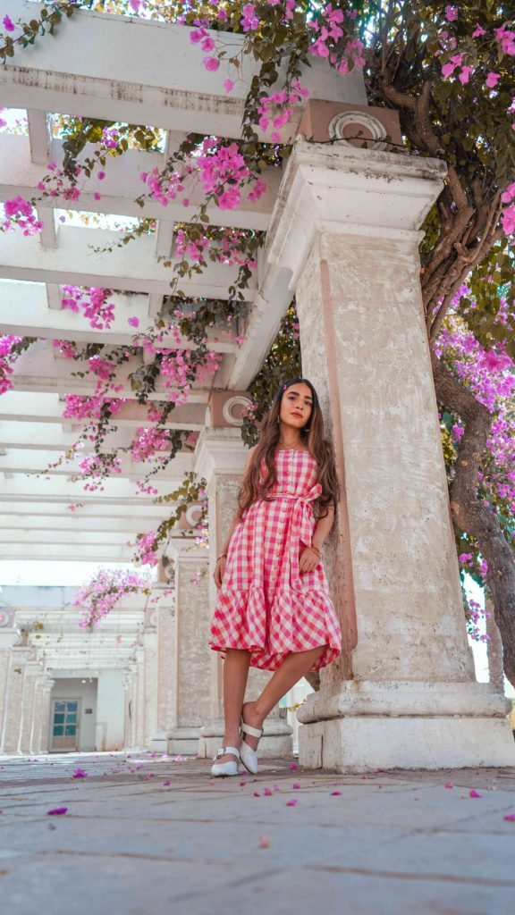 girl wearing pink gingham belted dress in a beautiful destination
