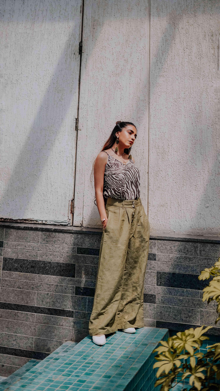 girl soaking in the sun wearing zebra print top & linen green pants