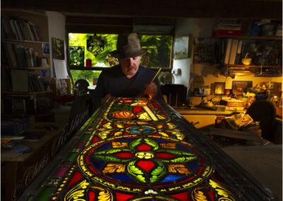 Stained glass window maker repairing Cornish church window in his workshop.
