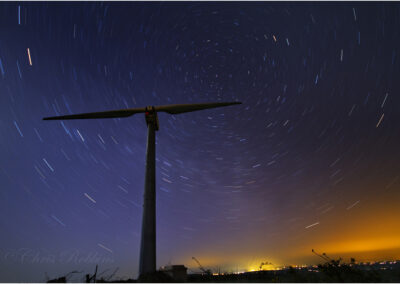 Two bladed wind turbine with star trails as the earth revolves