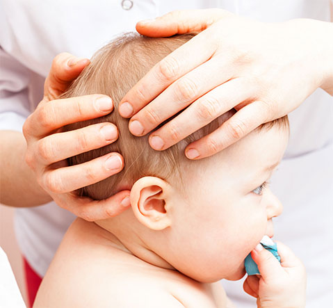 Baby treating by an osteopath, hands on his head