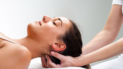 woman layed while an osteopath puts his hands under her head