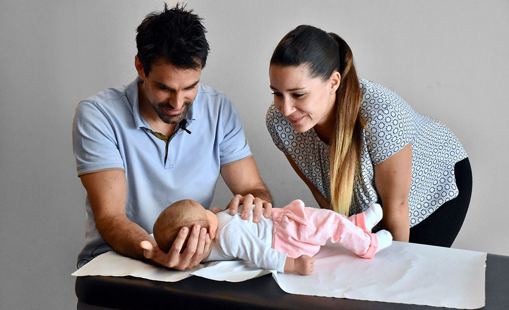 New born treated by osteopath, baby is lying on the table, osteopath's hands on his body, baby's mum is looking at her baby