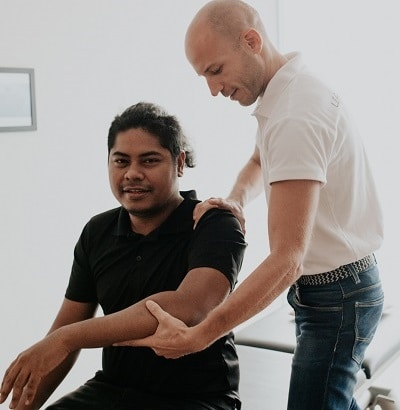 Osteopath trating a patient about carpal canal syndrome, checking on your whole body in order to improve its general