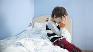 A young boy is crying because he made wee in his bed