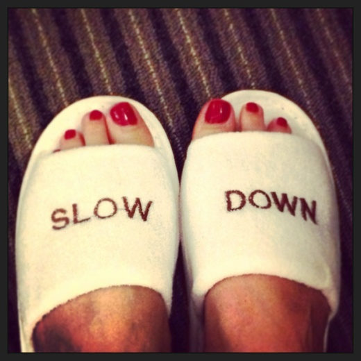 """Slippers with the words """"slow down"""" on them"""