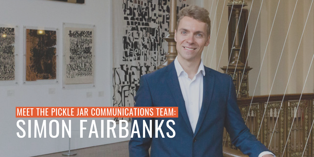 A professional photo of Simon Fairbanks who is wearing a suit next to a stairwell with artwork behind him