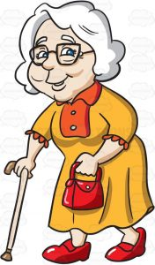 An old woman with white hair, wearing a black rimmed eye glasses, yellow with orange dress, red shoes and bag on her left hand, smiles while walking, with the help of her cream colored cane
