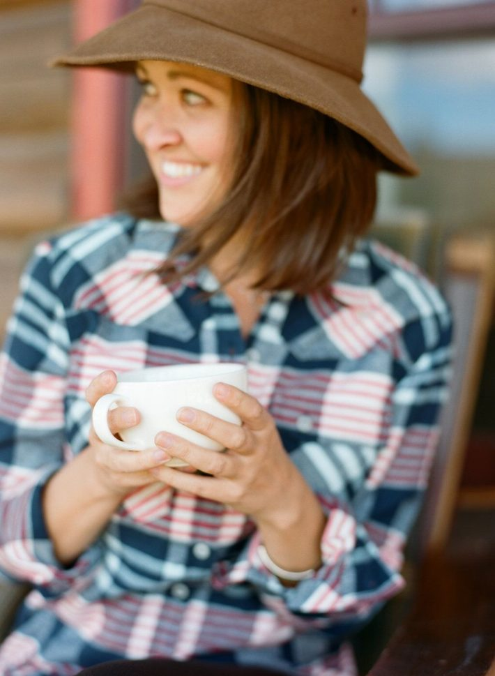 Mountain Town Blogger Meagan Murtagh enjoys coffee in a Stio flannel at Turpin Meadow Ranch in Jackson Hole Wyoming