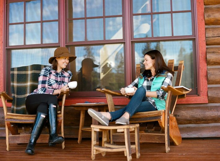 Jackson Hole Blogger Meagan and friend sit on the porch of Turpin Meadow Ranch sipping coffee
