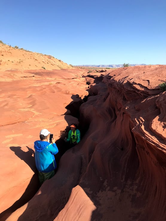 A tourist peeks out the top of Antelope Canyon