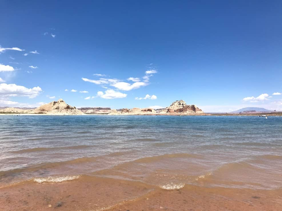 Large white rocks at Lake Powell sit in the background with the blue waters of Lake Powell in front