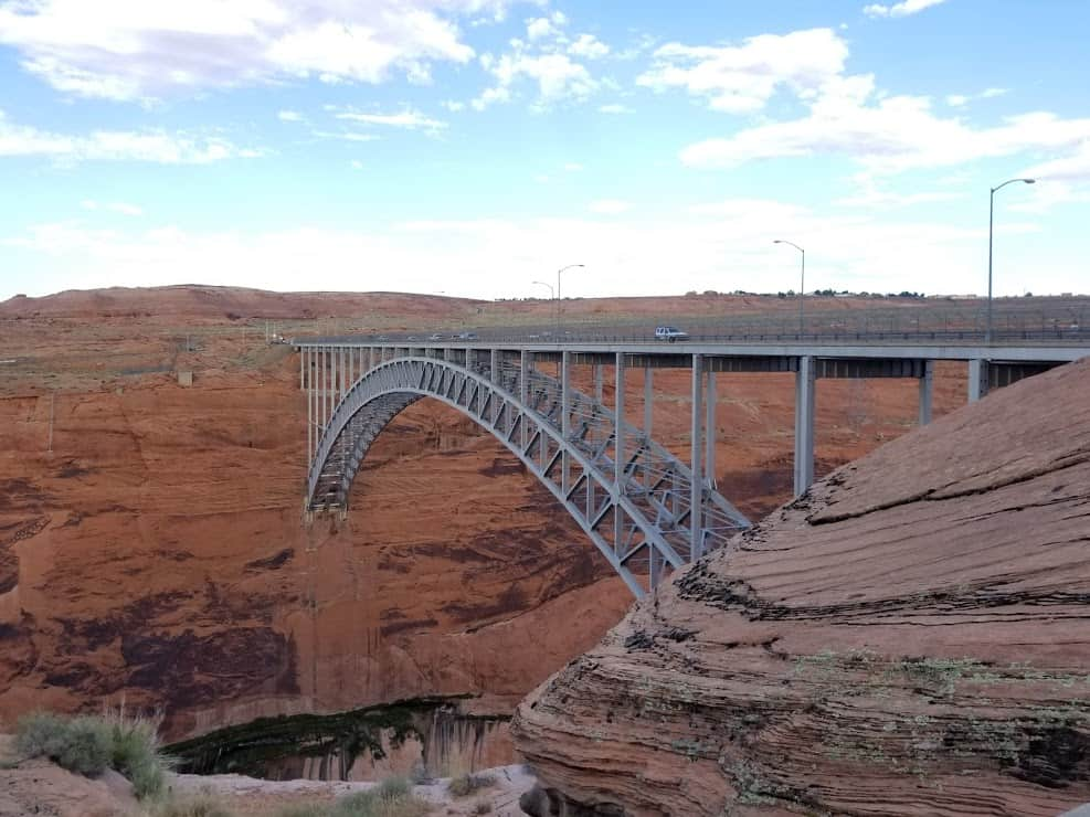 The Glen Canyon Dam Bridge stretches over Lake Powell's red cliffs.