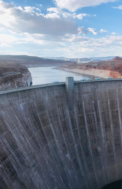 view of the sloping walls of concrete of the Glen Canyon Dam with Lake Powell sitting above it