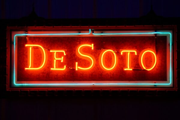 Lighted DeSoto framed red and blue neon sign.