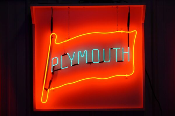 Lighted Plymouth red and aqua flag neon sign.