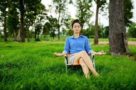 Business woman meditating and doing yoga in green field representing corporate wellness in Lewis Center, OH by FastTrack2