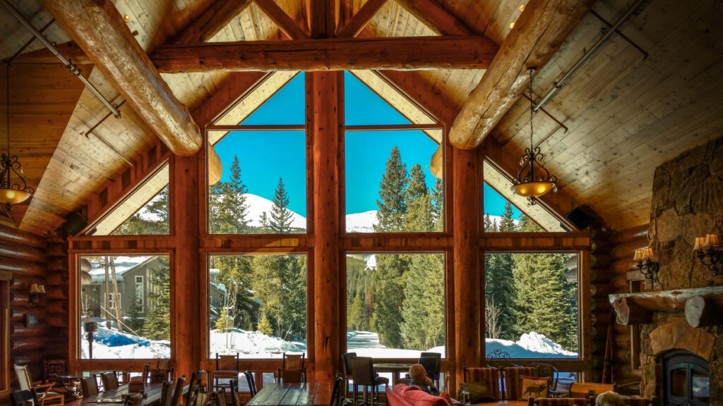 Wooded lodge interior with vaulted ceilings and large triangular-shaped window overlooking snow, pine trees and mountains at Breckenridge Nordic Center.