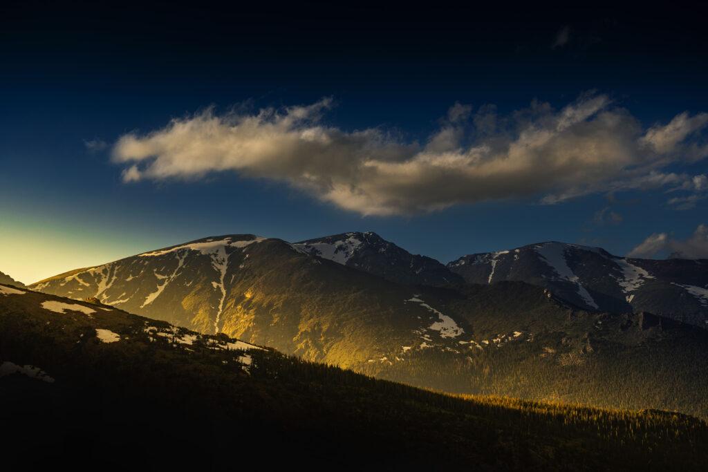 The sun sets at Mt. Chiquita, Ypsilon Mountain and Fairchild Mountain in Rocky Mountain National Park.