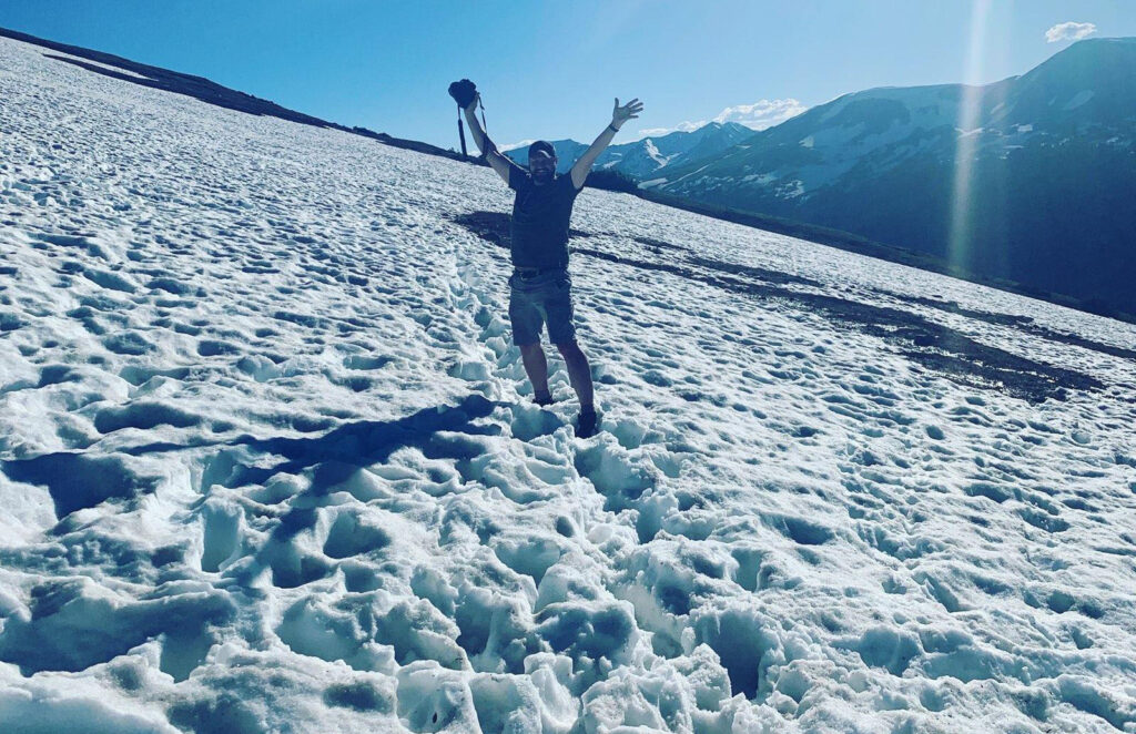 Andrew raises his arms happily while standing in ankle-high snow on the Western Ute Trail at Rocky Mountain National Park.