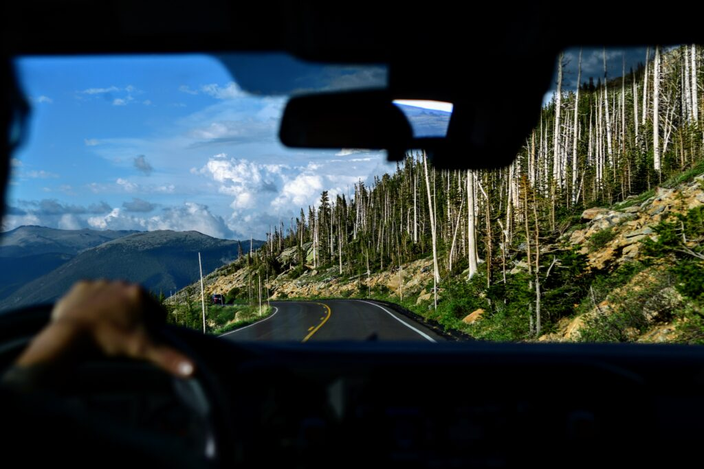 View from inside the cab of a truck of a road, mountains and aspens.