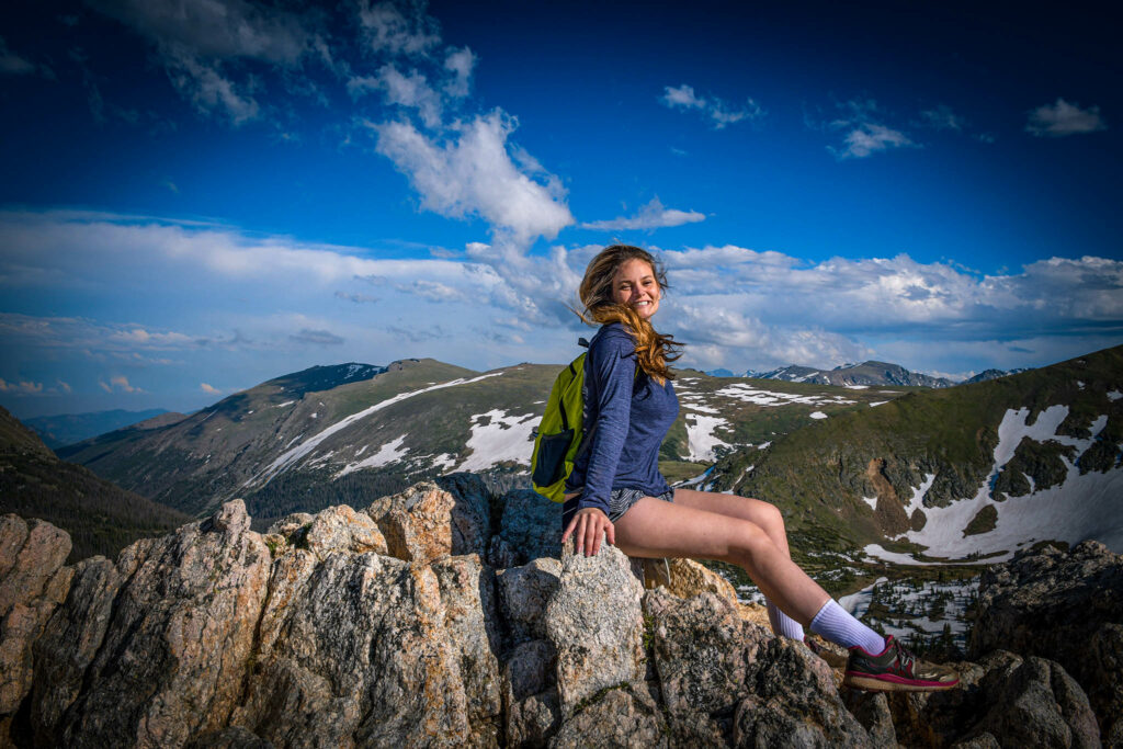 Kat sits atop a rocky outcropping with mountains in the background at the Alpine Ridge Trail summit at Rocky Mountain National Park.