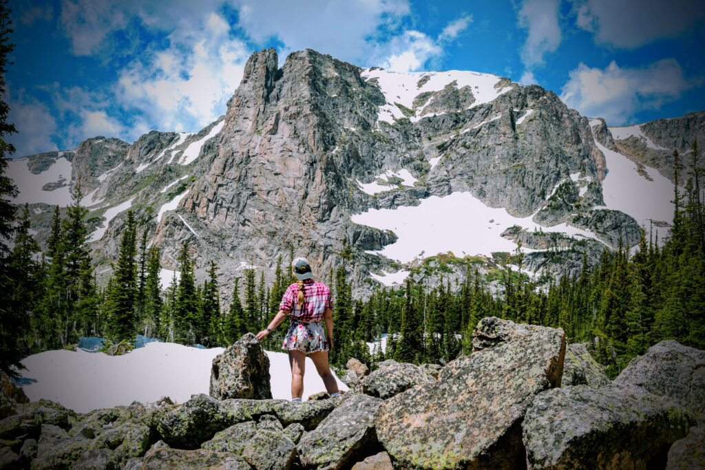 Kat stands before Notchtop Mountain on the trail to Lake Helene at Rocky Mountain National Park.