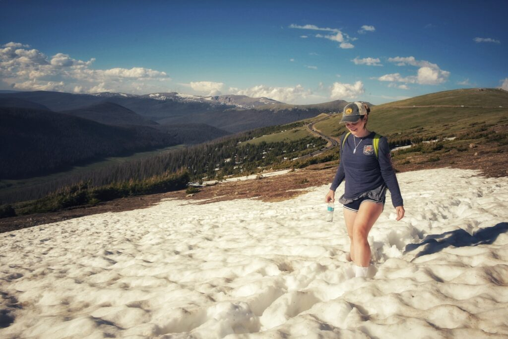 Kat walks through a snow bank on the Western Ute Trail at Rocky Mountain National Park.