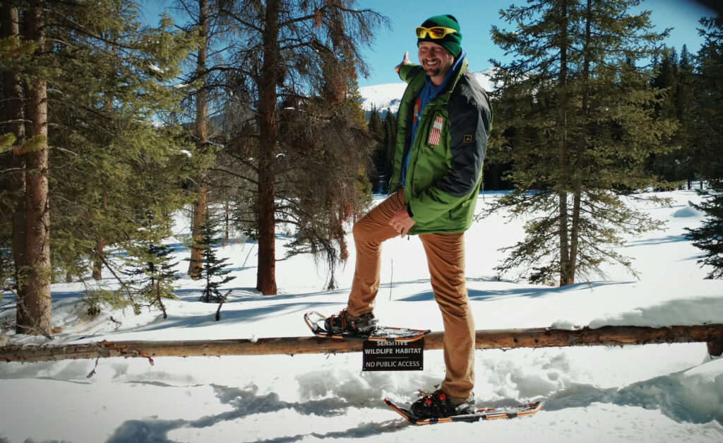 Andrew snowshoeing in a snowy wooded area with mountains in the background in Breckenridge.