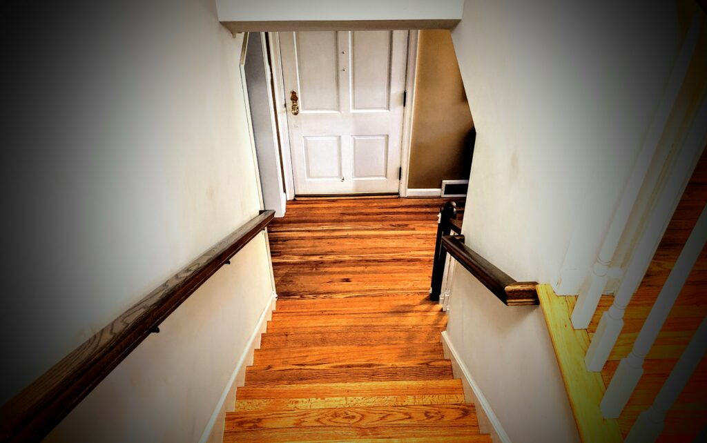 Looking down a staircase in a house with hardwood floors and white walls.