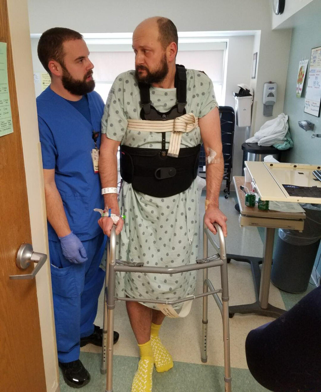 Andrew walking with the help of a walker and a physical therapist in a hospital room.
