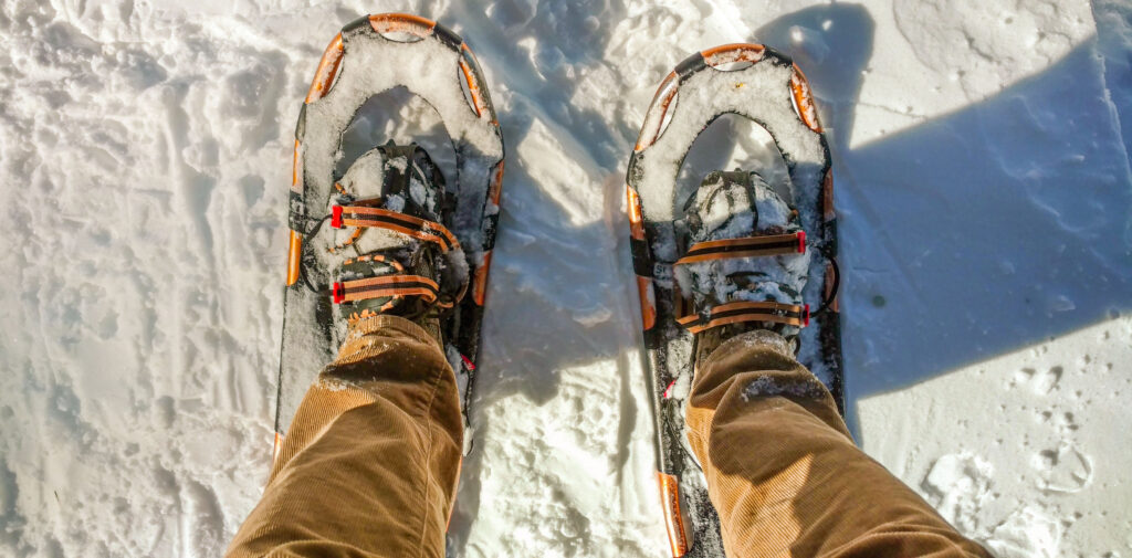 Looking down at Andrew's feet in snowshoes surrounded by snow.