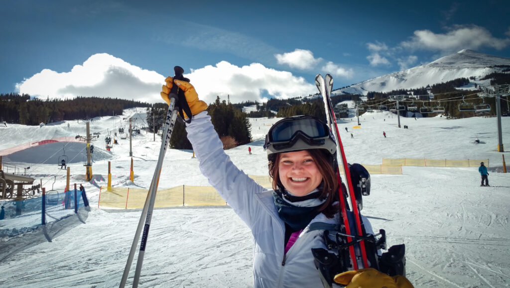 Kat holds her skis and poles triumphantly with a snowy ski slope and mountains in the background.