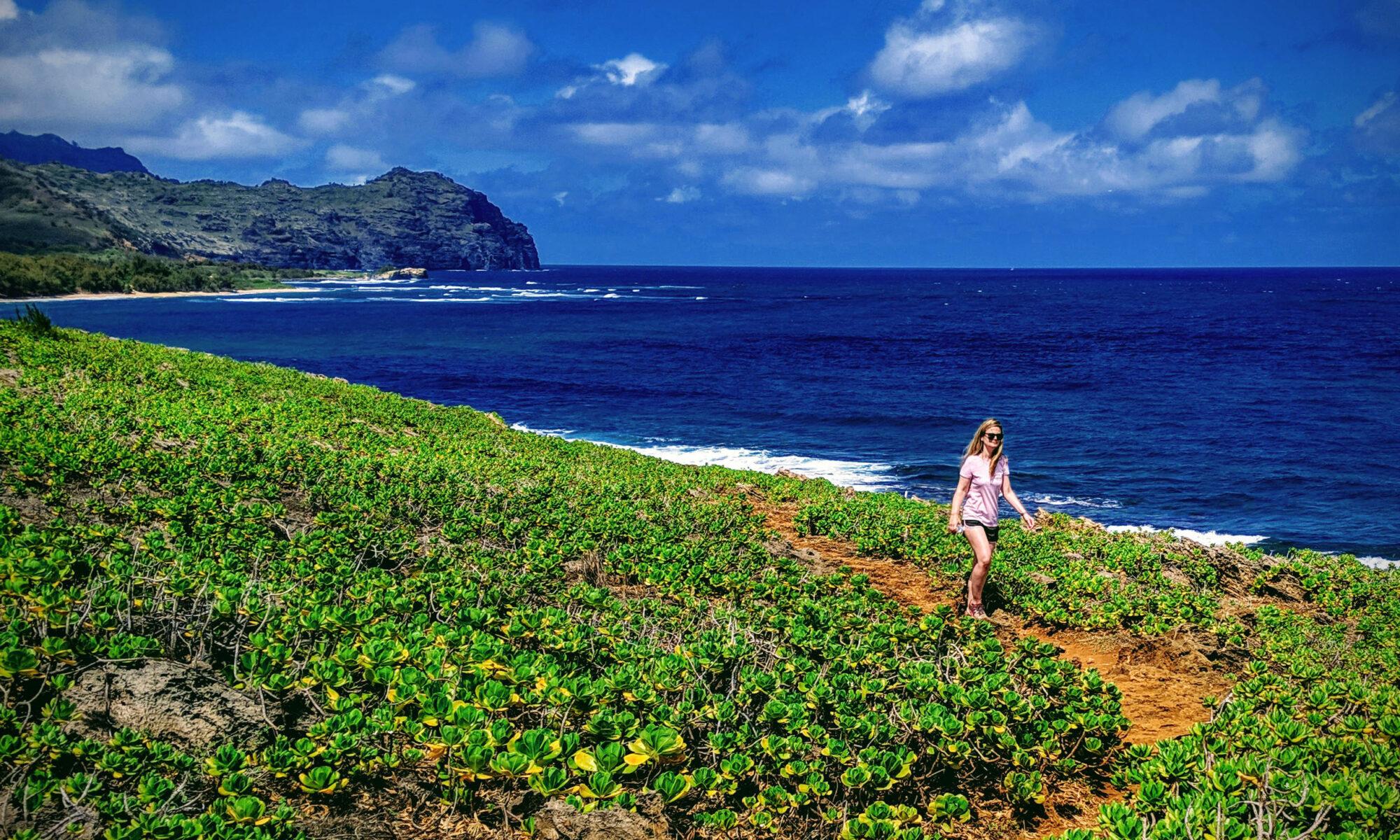 Woman hiking Maha'ulepu Heritage Trail along the ocean shore of Kauai, Hawaii.