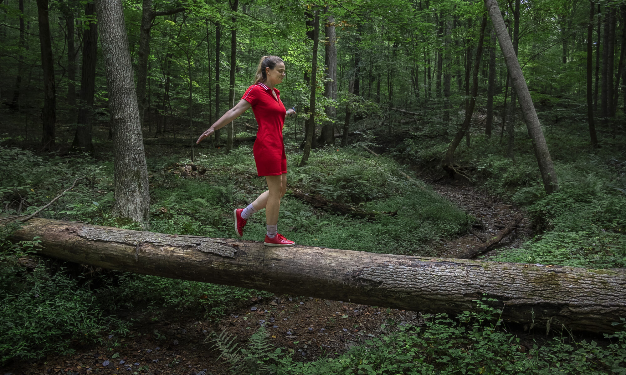 Woman in red dress walking across a fallen tree over a creek bed in the forest.