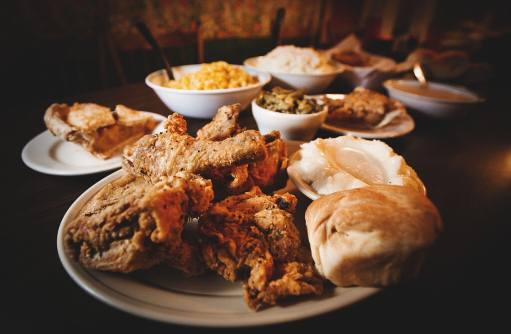 Plate of fried chicken with mashed potatoes, gravy and a biscuit, surrounded by side orders.