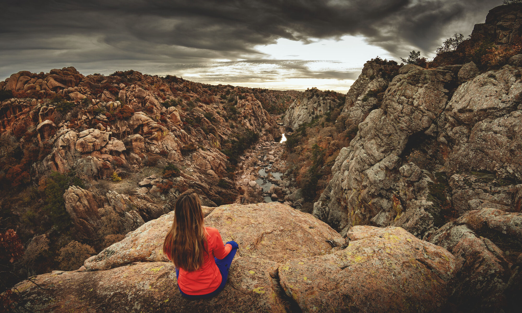 Woman hiker sitting on edge of cliff overlooking The Narrows canyon at Wichita Mountains Wildlife Refuge in Oklahoma.
