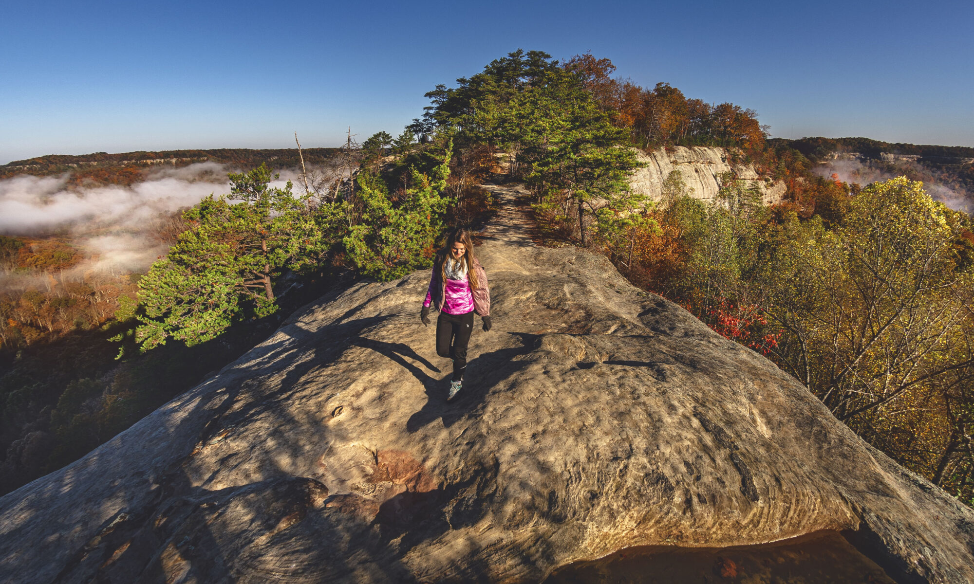 Woman hiking on Auxier Ridge with cliffs on both sides in Red River Gorge, Kentucky