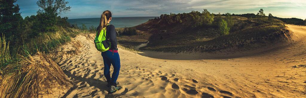 Woman hiker standing high atop sand dune overlooking vast Lake Michigan, Indiana Dunes State Park.