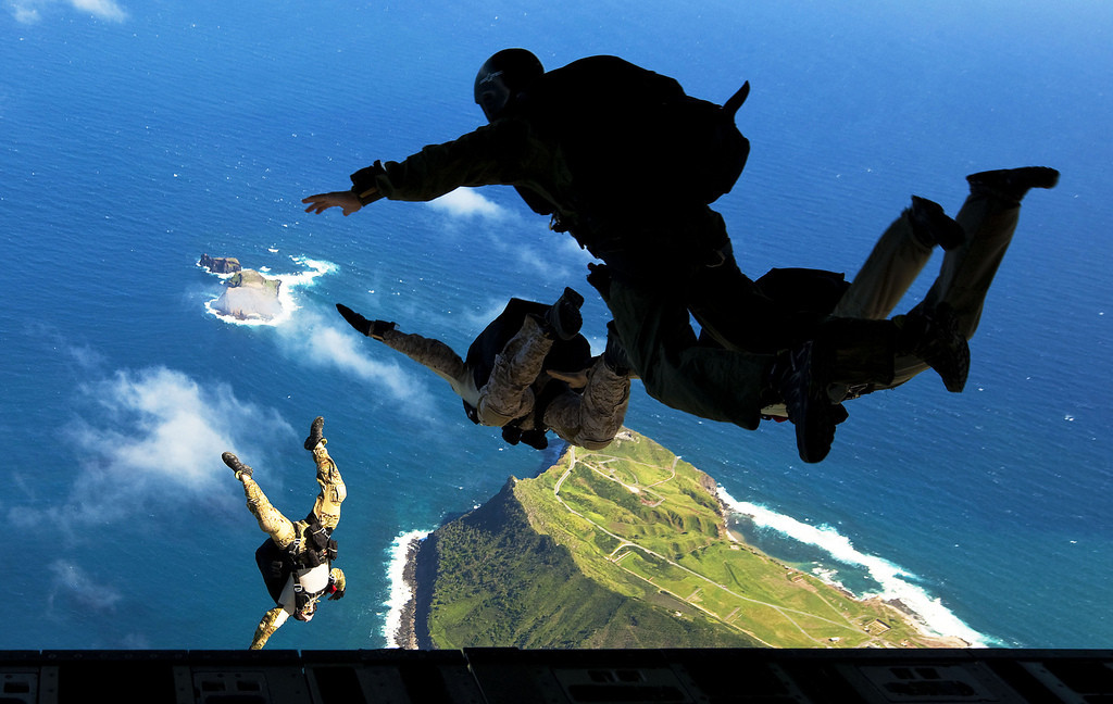Air Force pararescuemen from 103rd Rescue Squadron, 106th Rescue Wing, New York Air National Guard, and West Coast-based Navy SEALs leap from the ramp of an Air Force C-17 transport aircraft during free-fall parachute training over Marine Corps Base Hawaii, Jan. 21, 2011. The pararescuemen and SEALs parachuted from an Air Force C-17 transport aircraft over Marine Corps Base Hawaii to fulfill specialty-based sustainment training requirements. They were joined by Marines from 4th Force Reconnaissance Company, 4th Marine Division.