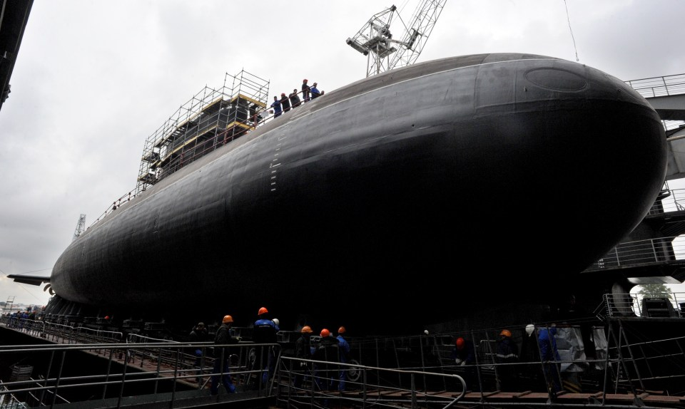 "Workers attend the launching ceremony of the Russian diesel-electric attack submarine Stary Oskol on Admiralty Shipyard in Saint Petersburg on August 28, 2014. Submarine ""Stary Oskol"" Project 636 is the third in the series, built to deliver the Russian Black Sea Fleet. Stary Oskol belongs to the Improved Kilo by NATO classification. AFP PHPOTO / OLGA MALTSEVA (Photo credit should read OLGA MALTSEVA/AFP/Getty Images)"