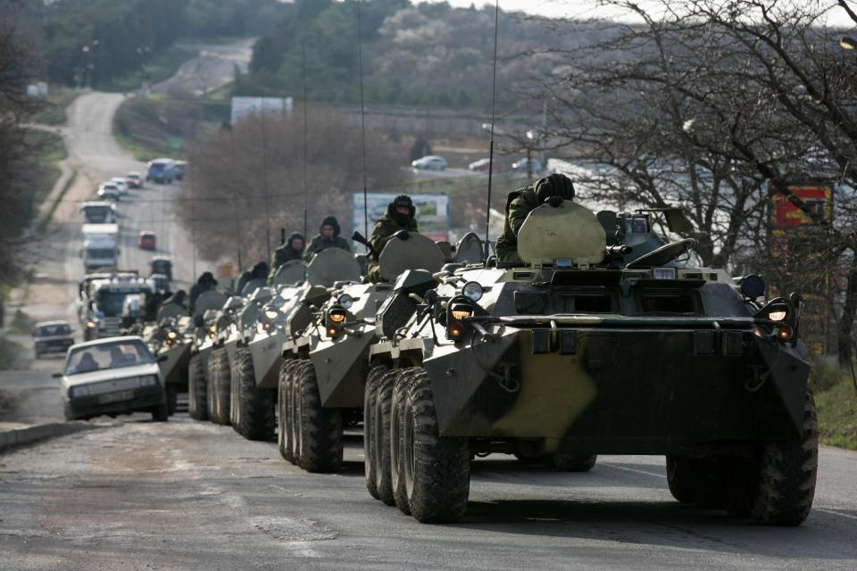 Soldiers, believed to be Russian, ride on military armoured personnel carriers on a road near the Crimean port city of Sevastopol March 10, 2014. REUTERS/Baz Ratner (UKRAINE - Tags: TPX IMAGES OF THE DAY MILITARY POLITICS)